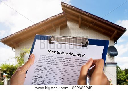 Person Filling Real Estate Appraisal Form In Front Of House