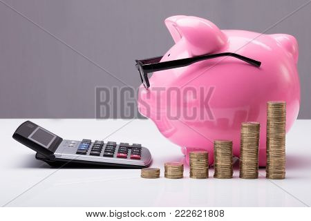 Stacked Coins In Front Of Pink Piggy Bank With Eye Glasses And Calculator On Desk