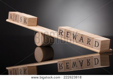Close-up Of A Wooden Seesaw Showing Imbalance Between Risk And Reward On Grey Background