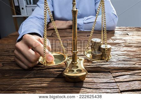 Close-up Of A Businessperson Balancing Stacked Coins On Justice Scale With His Finger
