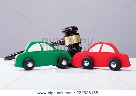 Green And Red Car In Front Of Gavel Against Grey Background