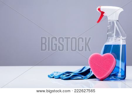 Blue Transparent Cleaning Solution In A Plastic Container With Heart Shape Sponge And Rubber Gloves