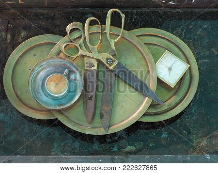Huge metal scissors 2 pieces lie side by side on copper round dishes, on the left are old round pocket watches, on the right is a vintage alarm clock, modern interior design of wall paintings.