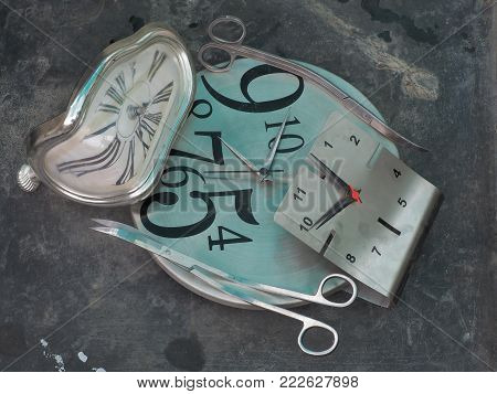 Silver long curved scissors for shearing plants among the deformed dials of a gray watch, fantastic picture.