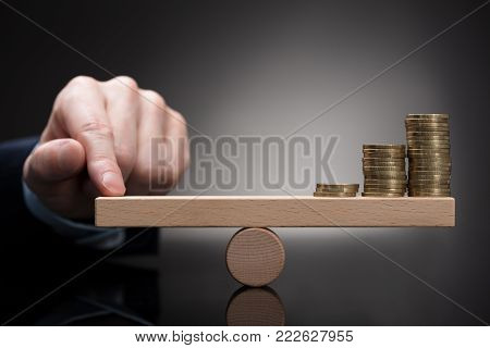 Close-up Of A Finger Balancing Stacked Coins On Seesaw Against Grey Background