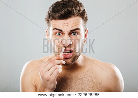 Horizontal picture of scared man removing nose hair with tweezers, isolated over gray background