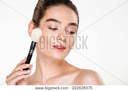 Beauty portrait of charming young female with fresh skin applying makeup using soft brush, with face downward isolated over white background
