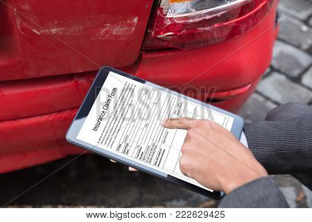 Insurance Agent's Hand Filling Insurance Claim Form On Digital Tablet After Car Accident
