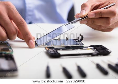 Close-up Of A Technician's Hand Fixing Damaged Screen On Mobile Phone