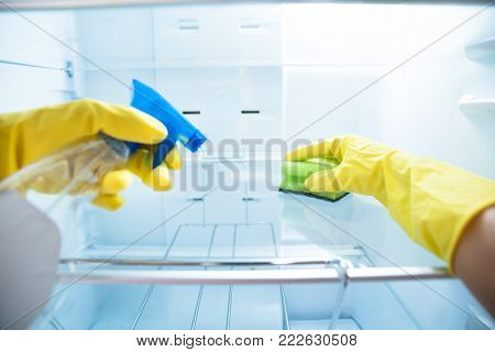 Close-up Of Woman's Hand Wearing Yellow Gloves Cleaning Open Refrigerator With Spray Bottle And Sponge
