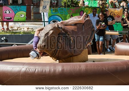 ATLANTA, GA - SEPTEMBER 2017:  A young man desperately tries to stay on a mechanical bull as he starts to fall, at the East Atlanta Strut, a fall festival in Atlanta, GA on September 23, 2017.