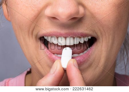Close-up Of A Woman Taking Medicine Pill
