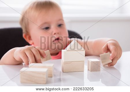 Close-up Of A Cute Baby Girl Making House From Wooden Blocks On Table