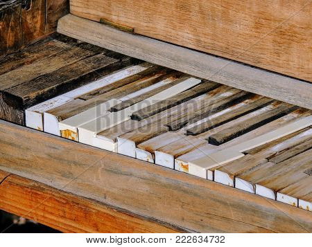 Close up of piano keys of an upright antique broken rustic piano outdoors in Arizona desert