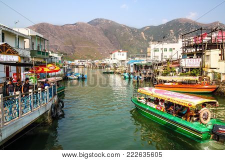 HONG KONG - APR 11, 2011: A sightseeing tour boat carrying visitors cruises along Tai O River where traditional houses built on stilts above the tidal flats of Lantau Island are homes to the Tanka people in this old fishing village of Hong Kong.