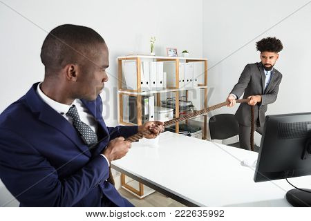 Two Young Businessmen Playing Tug Of War Over Desk At Workplace