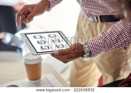 business, web design and technology concept - close up of designer with user interface on tablet pc computer screen at office