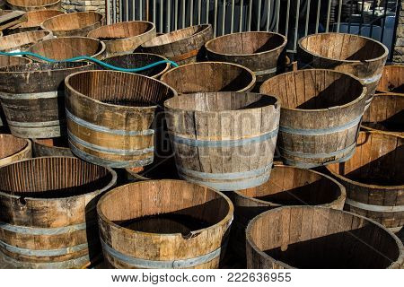 Stacked Old Wooden Half Barrels At Gerden Store Is About To Have Second Life As A Flower Planters Or