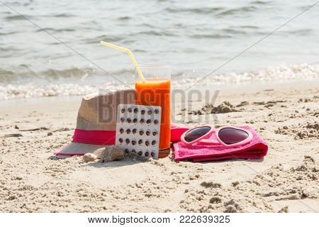 Medical pills, carrot juice and accessories for sunbathing on sand at beach, concept of prevention of vitamin A deficiency, beautiful and lasting tan