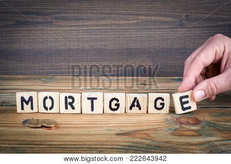mortgage. Wooden letters on the office desk, informative and communication background.