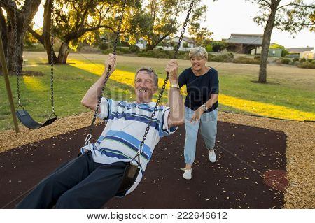 playful and happy senior American couple around 70 years old enjoying at swing park with wife pushing husband smiling and having fun together in mature lifestyle and love concept