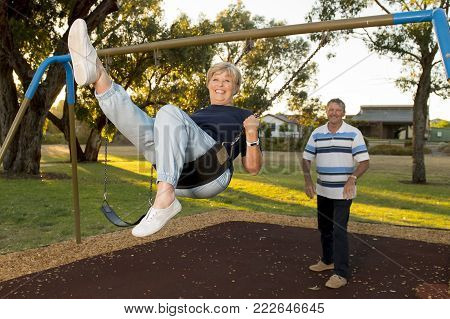 playful and happy senior American couple around 70 years old enjoying at swing park with husband pushing wife smiling and having fun together in mature lifestyle and love concept