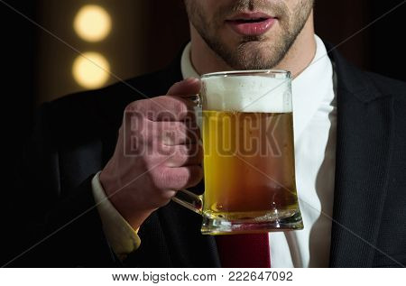 beer glass in hand of sommelier man with beard in formal outfit near mirror with lamps, meeting and relax, bar and restaurant, tasting and degustation