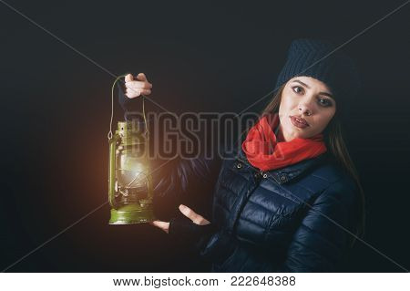 a woman holds a kerosene lamp in the hands