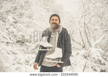 skincare and beard care in winter. Temperature, freezing, cold snap. Winter sport, Christmas. Bearded man smoking cigarette with skates in snowy forest. Man in thermal jacket, beard warm in winter.