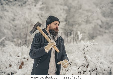 Temperature, freezing, cold snap, snowfall. Bearded man with axe in snowy forest. skincare and beard care in winter, beard warm in winter. Man lumberjack with ax. Camping, traveling and winter rest.