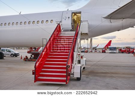 Airport runaway with airplane and stairway. Travel background. Sunset