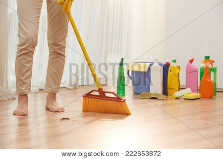 Unrecognizable barefoot woman sweeping floor with broom while wrapped up in housecleaning, detergent bottles, sponges and rags located in corner of room