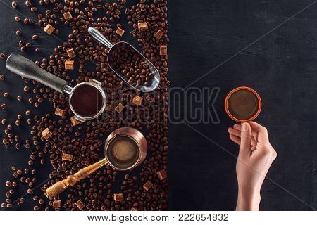 partial view of person holding cup of coffee and roasted coffee beans with coffee pot, scoop and sugar