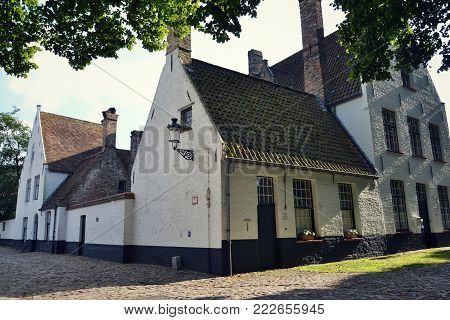 BRUGES, BELGIUM - JULY 15: White houses and green trees in Princely Beguinage Ten Wijngaerde complex on July 15, 2014 in Bruges, Belgium.