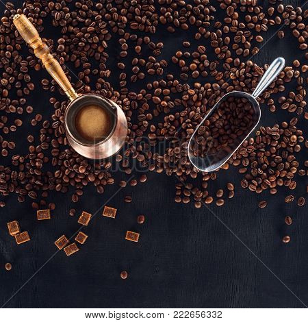 top view of roasted coffee beans, scoop and coffee pot on black