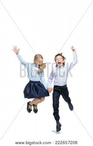 Happy excited schoolchildren in school uniform jumping for joy. Isolated over white background. School fashion. Copy space.