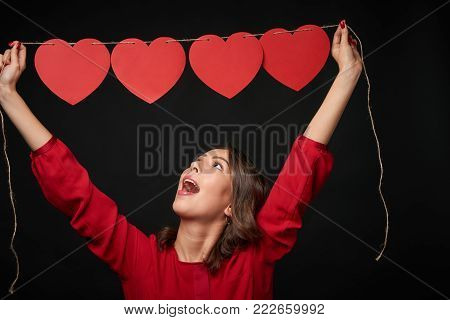 Woman in red lifting above her head a thread with four red heart shapes beaded on it, looking up in excitement, over dark background