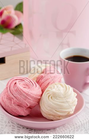 Homemade zephyr or marshmallow in pink plate with cup of coffee on white table. Marshmallow, Meringue, Zephyr. Valentine's or Mothers Day concept