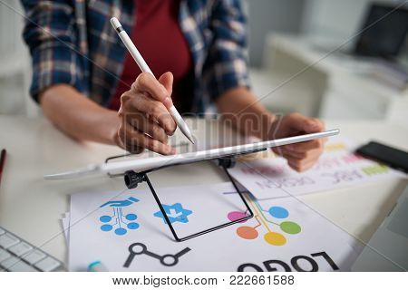 Close-up shot of unrecognizable graphic designer using stylus and digitizer while working on promising project, blurred background