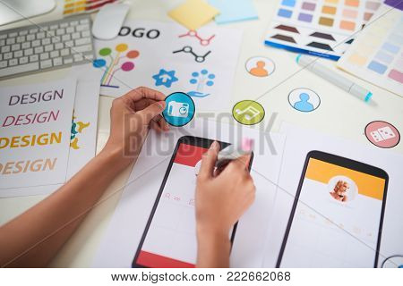 Creative young worker sitting at office desk and making colorful posters in order to visualize her ideas for colleagues, close-up shot