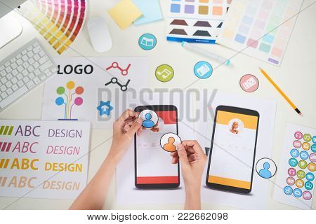 Close-up shot of unrecognizable manager wrapped up in making colorful poster for visual presentation while sitting at office desk