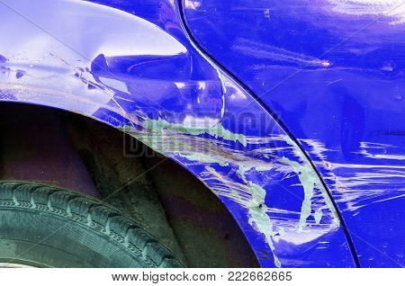 Car damage. Blue scratched car with damaged paint in crash accident or parking lot