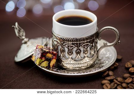 Traditional Turkish coffee in traditional metal cup on dark brown background with Turkish delight and bokeh