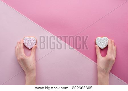 partial view of woman holding glazed cookies in hands on pink, st valentines day concept