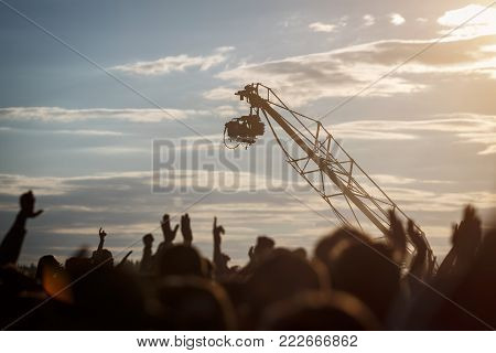 Silhouette of Television Camera hanging on crane is working on outdoor music festival, sunset background