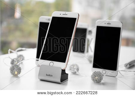 KIEV, UKRAINE - NOVEMBER 08, 2017: Modern iPhone 8 Plus Gold and Belkin stand on table against blurred background