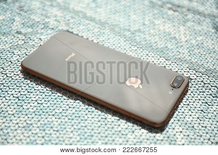 KIEV, UKRAINE - OCTOBER 25, 2017: Modern gold iPhone 8 plus on fabric with sequins
