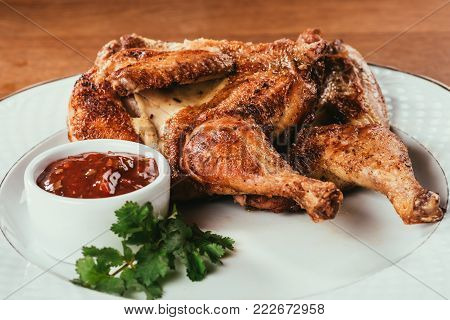 baked poultry laying on plate with sauce and herbs