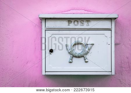 A locking white mailbox sits on a pink wall in Germany.