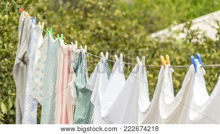 Laundry line with white clothes and green nature background. Laundry concept.